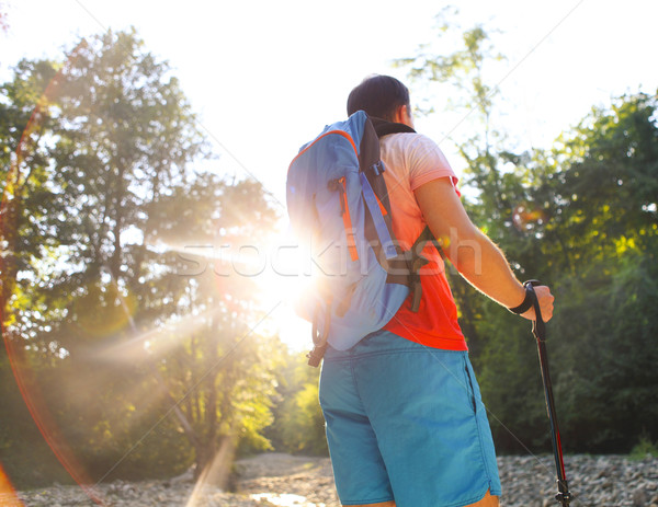Man hiking with backpac and sticks in mountains in sunset Stock photo © dashapetrenko