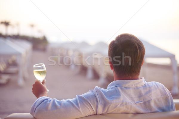 Stock fotó: Megnyugtató · férfi · tengerpart · üveg · fehérbor · nap