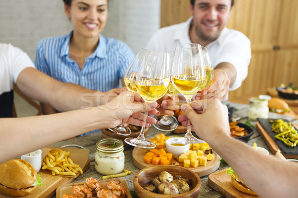 Stock photo: People with white wine toasting over served table with food.