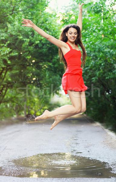 Genç mutlu kadın kırmızı elbise atlama Stok fotoğraf © dashapetrenko