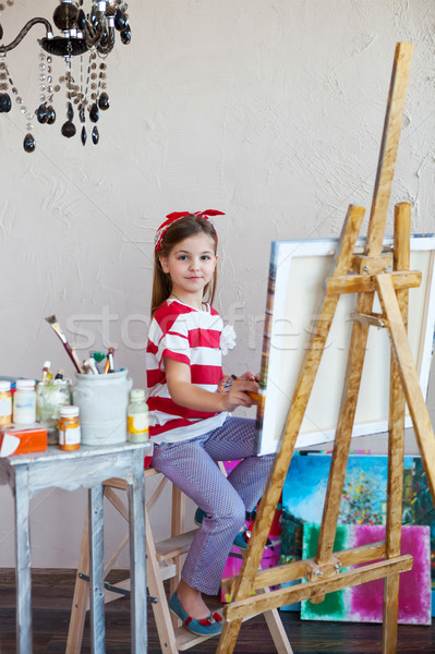 Little artist girl holding a paintbrush and looking over a canva Stock photo © dashapetrenko