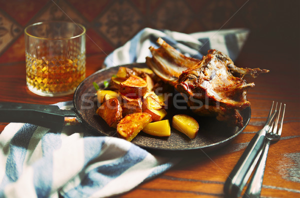 Braised goat meat with sauce and roasted potatoes in the pan Stock photo © dashapetrenko