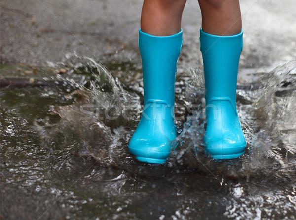 Child wearing blue rain boots jumping into a puddle Stock photo © dashapetrenko