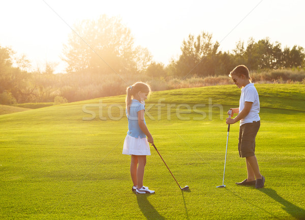 Enfants golf domaine clubs de golf coucher du soleil Photo stock © dashapetrenko