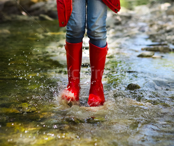 Child wearing red rain boots jumping. Close up Stock photo © dashapetrenko
