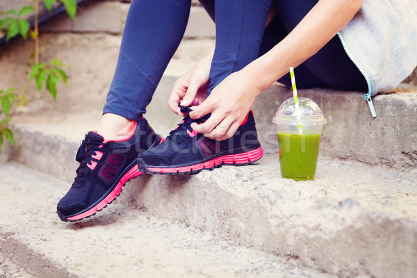 Stock photo: Green detox smoothie cup and woman lacing running shoes before w