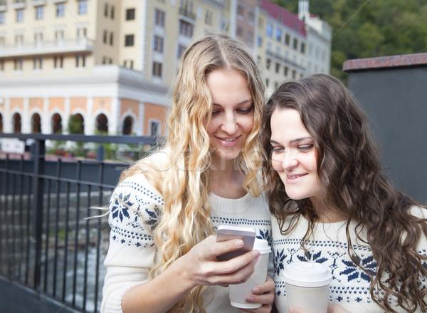 Two happy women friends sharing social media in a smart phone ou Stock photo © dashapetrenko
