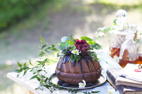 Cocolate cake decorated with flowers and three whiskey decanters Stock photo © dashapetrenko
