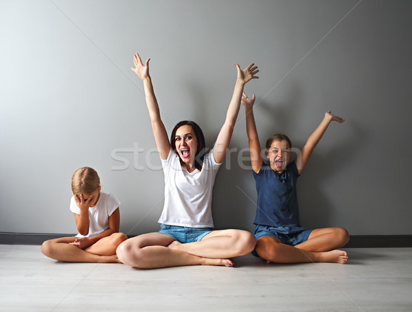 Happy mother and one of her daughters excited sitting in living  Stock photo © dashapetrenko