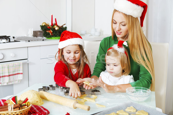 Two little girls and mother baking Christmas cookies in the kitc Stock photo © dashapetrenko