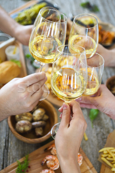 People with white wine toasting over served table with food. Stock photo © dashapetrenko