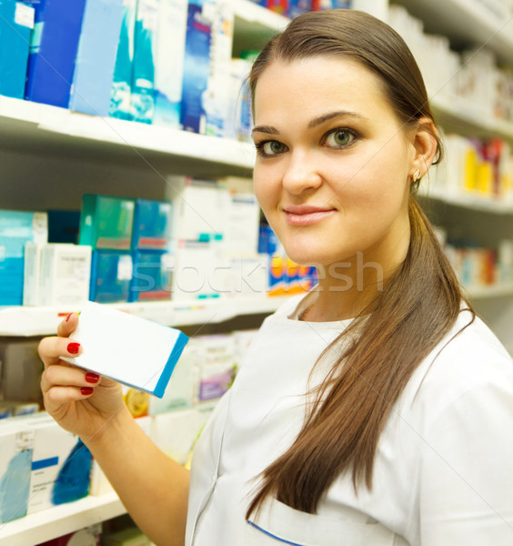 Pharmacist showing medicine box at pharmacy counter Stock photo © dashapetrenko