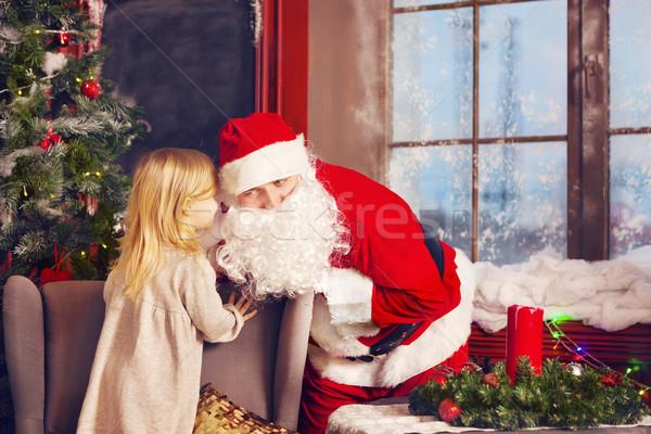 Little girl telling her Christmas wish in Santa Claus near the C Stock photo © dashapetrenko