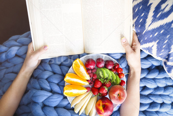 Plate with fresh fruit salad on a blue plaid and book. Woman rea Stock photo © dashapetrenko