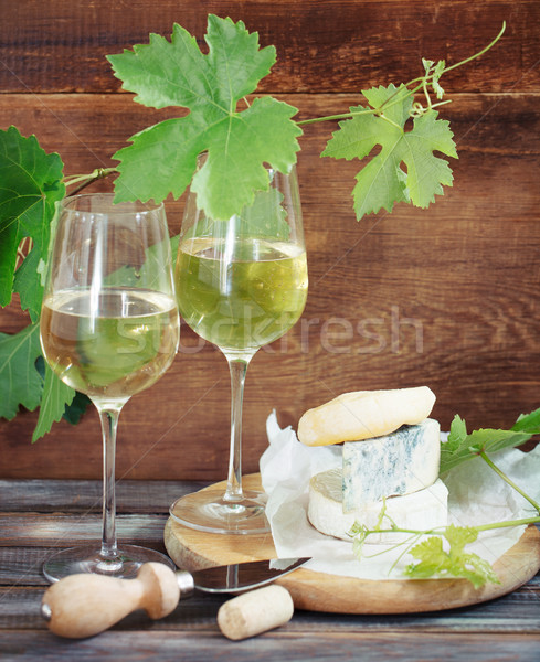 Glasses of white wine, bottle and cheese Stock photo © dashapetrenko