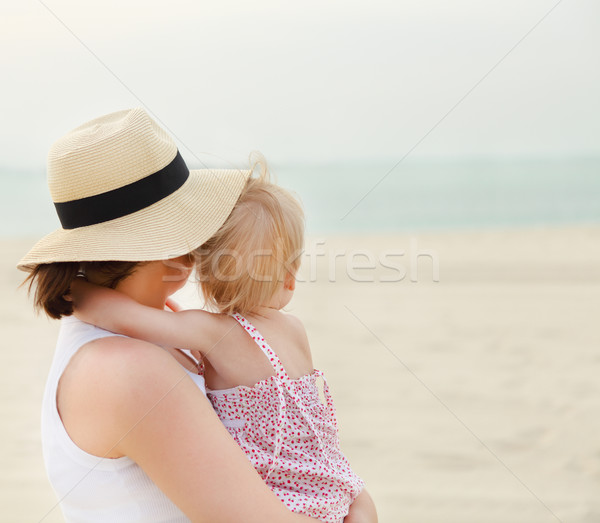 Portrait of mother holding her bay girl at beach Stock photo © dashapetrenko