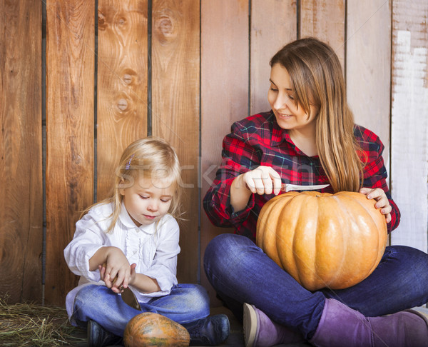 Mother and her little daughter carving Halloween pumpkins  Stock photo © dashapetrenko