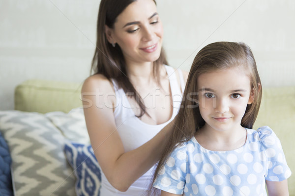 Adorable young family in living room. Mother combing her daughte Stock photo © dashapetrenko