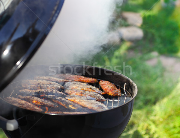 Fish fillets on the grill with flames Stock photo © dashapetrenko