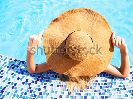Young woman lying on deckchair by swimming pool Stock photo © dashapetrenko