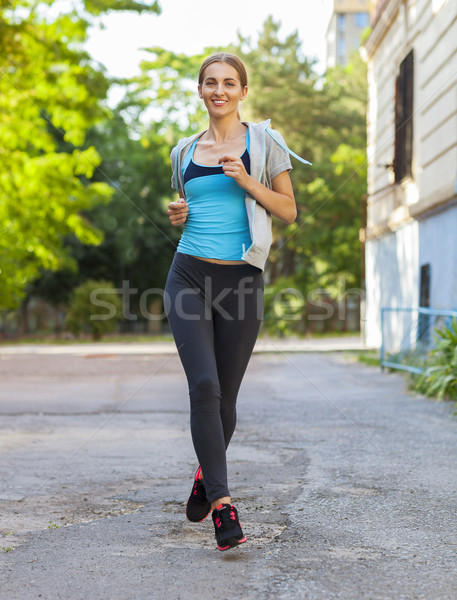 Young female runner in hoody is jogging in the city  Stock photo © dashapetrenko