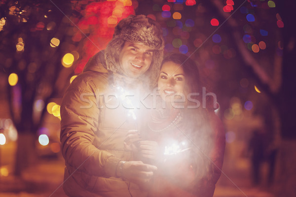 Young couple with Bengal light looking at camera outside Stock photo © dashapetrenko