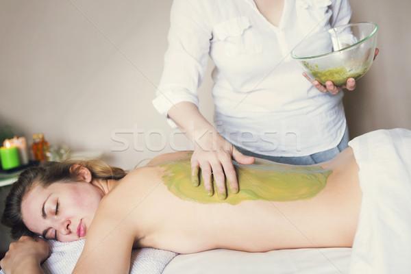 Beautiful relaxed woman having clay mask applying by beautician Stock photo © dashapetrenko