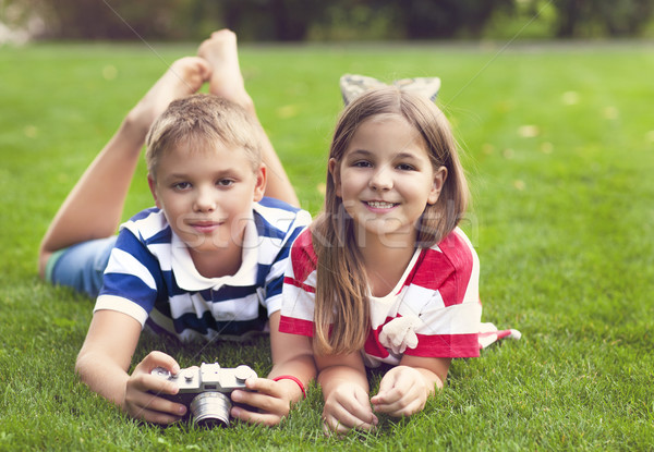 Pretty little brother and sister playing with a camera in summer Stock photo © dashapetrenko