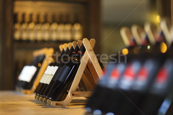 Wine bottles on a wooden shelf.  Stock photo © dashapetrenko
