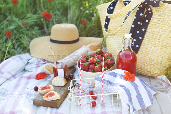 Basket, sandwiches, plaid and juice in a poppy field. Stock photo © dashapetrenko