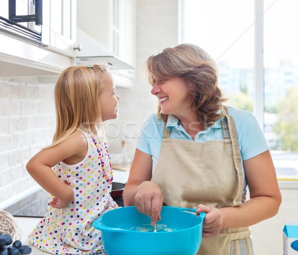 Cute little girl baking with her grandmother Stock photo © dashapetrenko
