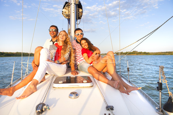 Smiling friends on yacht deck and greeting Stock photo © dashapetrenko