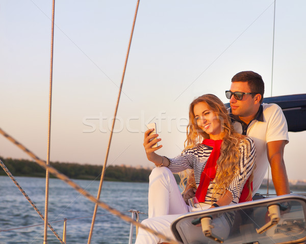 Beautiful couple taking a selfie on a sailing boat at summer  Stock photo © dashapetrenko
