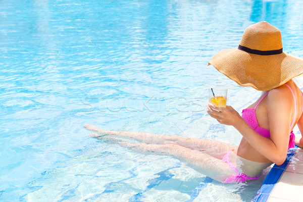 Pretty woman in a hat enjoying cocktail in a swimming pool Stock photo © dashapetrenko