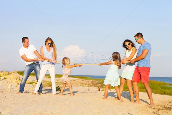 Tug of war - friends playing on the beach Stock photo © dashapetrenko