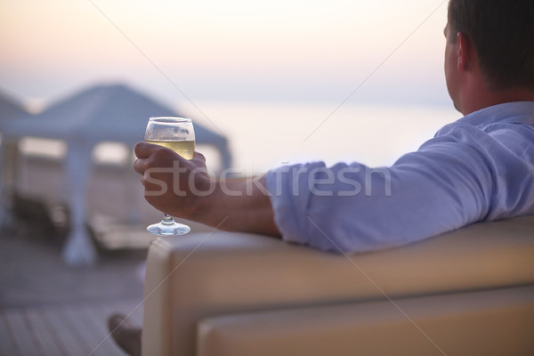 Relaxing man with glass of white wine on the beach Stock photo © dashapetrenko