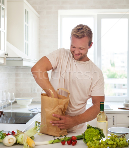 Man holding paper bag full of groceries on the kitchen  Stock photo © dashapetrenko