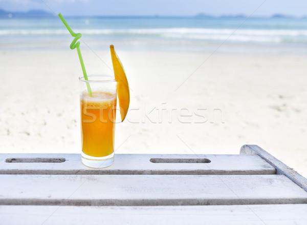 Glass of orange colour juice on the beach Stock photo © dashapetrenko