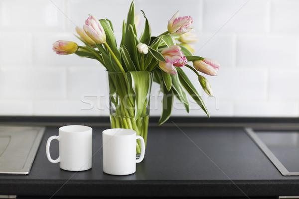 Pink tulips bouquet in glass vase on the kitchen Stock photo © dashapetrenko