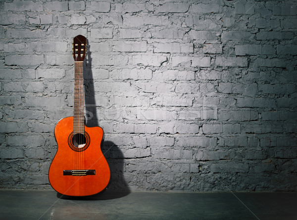 Acoustic guitar leaning on grungy wall Stock photo © dashapetrenko