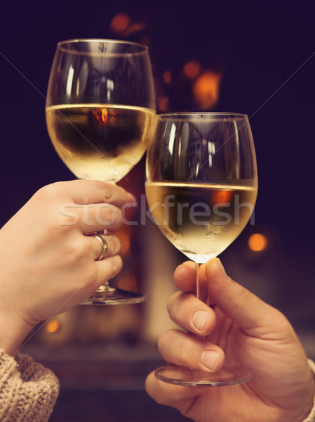 Couple toasting wineglasses in front of lit fireplace Stock photo © dashapetrenko