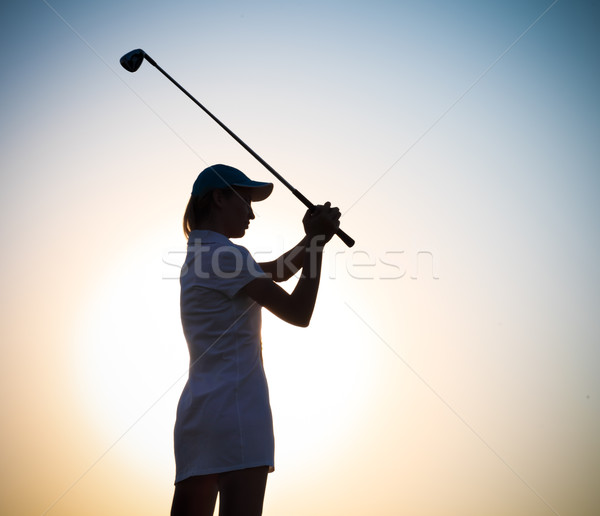 Female golfer at sunset Stock photo © dashapetrenko