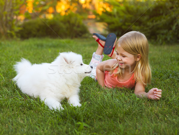 Little smiling girl playing with Samoyed puppy in the summer gar Stock photo © dashapetrenko