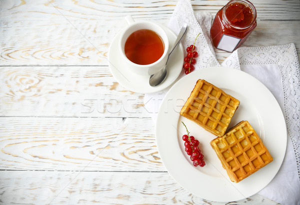 Waffles with red currant jam and berries on a white plate on the Stock photo © dashapetrenko