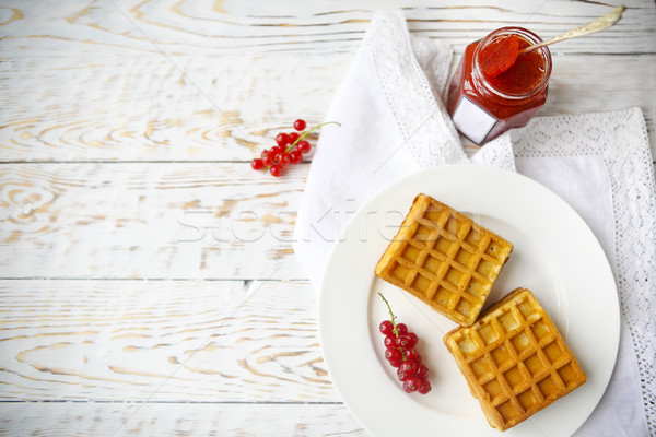 Waffles with red currant jam and berries on a white plate Stock photo © dashapetrenko