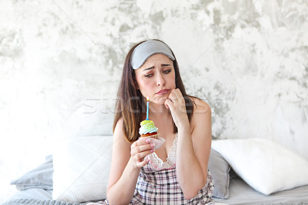 Sad woman on her Birthday holding cupcake in her bedroom Stock photo © dashapetrenko