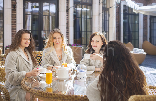 Four young women drinking tea at spa resort Stock photo © dashapetrenko