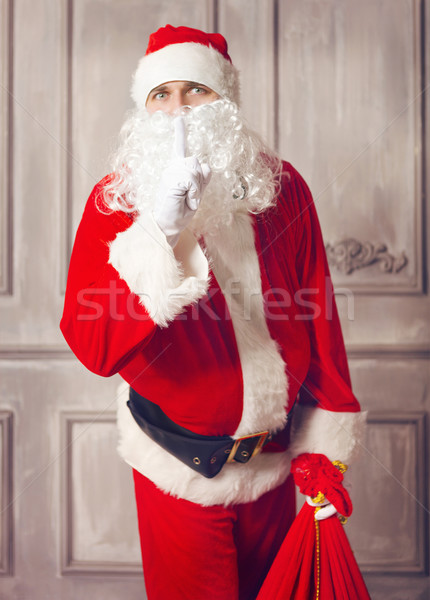 Photo of happy Santa Claus with big bag of presents looking at c Stock photo © dashapetrenko