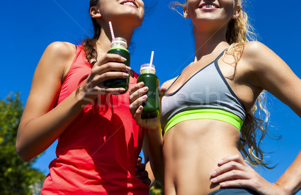 Two happy women drinking vegetable smoothie after fitness runnin Stock photo © dashapetrenko