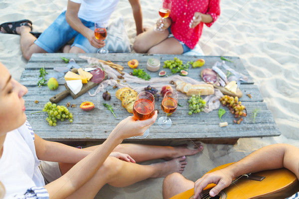 Young friends drinking rose wine on summer beach picnic Stock photo © dashapetrenko
